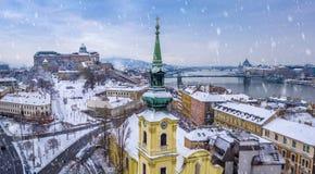 Budapest, Hungary - Catholic church with snowy Buda district, Buda Castle Royal Palace, Varkert Bazaar, Szechenyi Chain Bridge royalty free stock photo