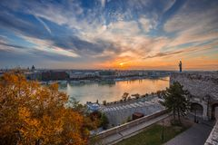 Budapest, Hungary - Colorful autumn trees at Buda Castle with skyline view of Budapest at sunrise. With beautiful clouds royalty free stock photo