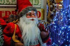 Christmas toy Santa Claus for sale in the store on the background of Christmas wreaths and lights from led lamps. BUDAPEST, HUNGARY - DECEMBER 20, 2017 stock photos