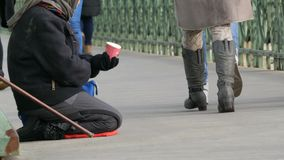 Budapest, Hungary - December 6, 2018: A hungry beggar woman sits on her lap next to a cane and beg for the alms