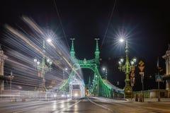 Budapest, Hungary - Festively decorated light tram Fenyvillamos on the move at Liberty Bridge Szabadsag hid by night. Christmas season in Budapest royalty free stock photography