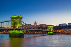 Budapest, Hungary - Green light illuminated Szechenyi Chain Bridge over River Danube and Buda Castle Royal Palace. At blue hour with clear blue sky royalty free stock photos