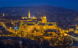 Budapest, Hungary - The Historic Royal Palace aka Buda Castle with Matthias Church. And the Buda Hills at background at blue hour royalty free stock photos