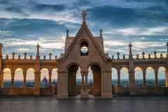 Budapest, Hungary - The Hungarian Parliament and city of Budapest throught the Fisherman`s Bastion. `s arch windows at sunrise with beautiful sky and clouds Stock Image