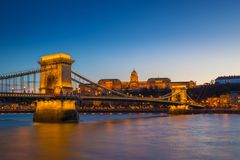 Budapest, Hungary - Illuminated Szechenyi Chain Bridge over River Danube and Buda Castle Royal Palace. At blue hour with clear blue sky stock image