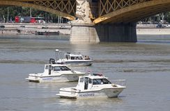 Budapest, Hungary – June 11, 2019; Police boat assure the area of the the raising action of the sunken Hableany tour ship. Budapest, Hungary – June royalty free stock photo