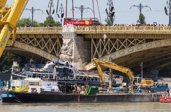 Budapest, Hungary – June 11, 2019; Raising action to the surface of the sunken Hableany tour ship. Red bus on the Margaret Bridge royalty free stock images