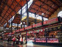 People shopping in the Great Market Hall in the section dedicated to butchers and meat produce. Budapest, Hungary - March 07, 2016: People shipping in the Great Stock Photography