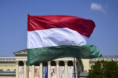 Flag of Hungary developing in the wind on the blue sky background stock photos