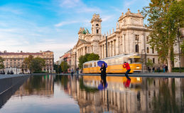 BUDAPEST, HUNGARY - OCTOBER 27, 2015: Budapest Parliament Square with Fountain water, moving tram, people and reflection. Stock Image
