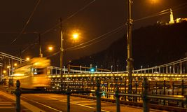 Night view of the city tram on the background of the Chain Bridge in Budapest, Hungary. Selective focus. Traveling to Hungary stock photo