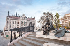 BUDAPEST, HUNGARY - OCTOBER 26, 2015: Parliament building and poet Attila Jozsef statue in Budapest, Hungary, Royalty Free Stock Photo