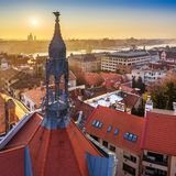 Budapest, Hungary - Old traditional metal tower and red rooftops of Castle District with rising sun, St. Stephens Basilica. And Szechenyi Chain Bridge in the stock photography
