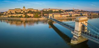Budapest, Hungary - Panoramic aerial view of Szechenyi Chain Bridge at sunrise with Buda Castle Royal Palace. Buda Tunnel, Sandor Palace and Fisherman`s royalty free stock photography