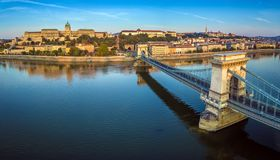 Budapest, Hungary - Panoramic aerial view of Szechenyi Chain Bridge at sunrise with Buda Castle Royal Palace. Buda Tunnel, Sandor Palace and Fisherman`s stock image