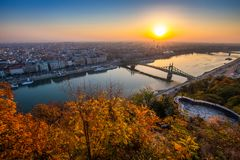 Budapest, Hungary - Panoramic skyline view of Budapest with beautiful autumn foliage, Liberty Bridge. Szabadsag Hid and lookout on Gellert Hill at sunrise stock photo
