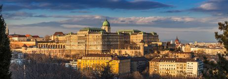 Budapest, Hungary - Panoramic skyline view of the beautiful Buda Castle Royal Palace with parliament of Hungary. At sunset with blue sky and clouds stock photography