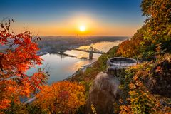 Budapest, Hungary - Panoramic skyline view of Budapest at sunrise with beautiful autumn foliage, Liberty Bridge. Szabadsag Hid and lookout on Gellert Hill royalty free stock photo