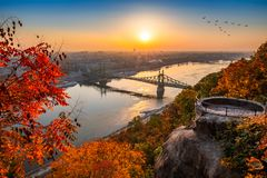 Budapest, Hungary - Panoramic skyline view of Budapest at sunrise with beautiful autumn foliage, Elisabeth Bridge. Erzsebet Hid, birds in the sky and lookout on stock images
