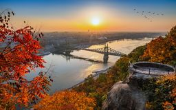 Budapest, Hungary - Panoramic skyline view of Budapest at sunrise with beautiful autumn foliage, Liberty Bridge. Szabadsag Hid, birds in the sky and lookout on royalty free stock images