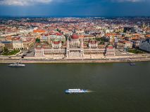 Budapest, Hungary - Sightseeing boat on River Danube with the Houses of Parliament building and skyline of Budapest. At daytime on an aerial photograph royalty free stock images