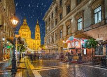 Budapest, Hungary - Snowy night at a Christmas market and shopping street with street-lamp, festive decoration. And St.Stephen`s basilica at background royalty free stock images