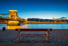 Budapest, Hungary - Traditional red bench at the riverside with illuminated Szechenyi Chain Bridge, Buda Castla Royal Palace Stock Photos
