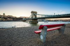 Budapest, Hungary - Traditional red bench at the riverside with Szechenyi Chain Bridge, Buda Castle Royal Palace. And sightseeing boat on River Danube at sunset royalty free stock photos