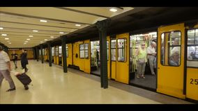Budapest Hungary vintage old metro train stop underground. Yellow train in Budapest metro. Interior of metro station in stock video