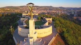 Budapest, Hungría - cantidad aérea 4K del vuelo alrededor de la estatua de la libertad con el horizonte de Budapest metrajes