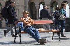 Budapest, Hungría - 8 de abril de 2018: Hombre barbudo joven que se sienta en un banco de parque de madera que planea su movimien imagenes de archivo