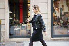 Budapest, Hungría - 5 de abril de 2018: Muchacha que camina abajo de la calle con su teléfono ella está mirando su teléfono elega imágenes de archivo libres de regalías