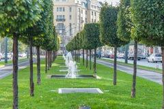 BUDAPEST, HUNGRÍA - 26 DE OCTUBRE DE 2015: Fuente en el medio de la manera de la tranvía en árboles del verde de Budapest en fond Imágenes de archivo libres de regalías
