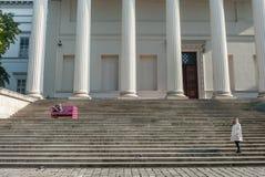 BUDAPEST, HUNGRÍA - 26 DE OCTUBRE DE 2015: Palacio de Budapest con la gente local que se sienta en el banco y la lectura colorido Fotografía de archivo libre de regalías