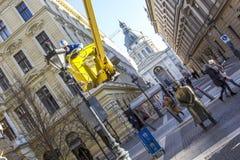 BUDAPEST, HUNGRÍA - ENERO DE 2017: Trabajador que substituye bulbos viejos en el alumbrado público de la linterna por nuevos Fotografía de archivo