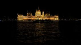 Budapest National Parliament illuminated at night. Danube river in foreground stock footage