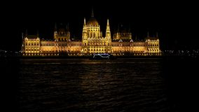 Budapest National Parliament illuminated at night. Danube river in foreground stock video