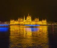 Budapest parlament på den kalla vinternatten med fartyg som passerar på Donau Arkivbild