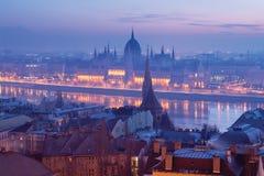 Budapest parlamentbyggnad i blå ogenomskinlighet över floden Royaltyfri Bild