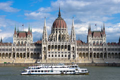 Budapest: Sightseeing Boat And Hungarian Parliament Building. Budapest: a sightseeing boat passes in front of the symmetrical building of the Hungarian Stock Photos
