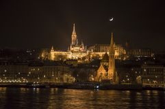 Budapest,  St. Matthias church and St. Anna church. View from Buda  over Danube to the church of St. Mathias at night. Illuminated by lights Stock Photos