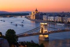 Budapest-Stadtbildsonnenuntergang mit Hängebrücke-und Parlaments-Gestalt Stockfoto