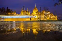 Budapest, Ungarn - belichtetes Parlament von Ungarn an der blauen Stunde mit Reflexion und traditioneller gelber Tram stockfotografie