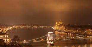 Budapest, Ungarn bis zum Nacht - Hängebrücke, ungarische Parlaments-Gebäude- und Margaret-Brücke lizenzfreie stockfotografie