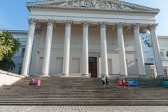 BUDAPEST, UNGARN - 26. OKTOBER 2015: Budapest-Palast mit den lokalen Leuten, die auf der bunten Bank und dem Ablesen sitzen Touri Stockfotografie