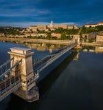 Budapest, Ungarn - Sonnenaufgang über Szechenyi-Hängebrücke mit Buda Castle Royal Palace am Hintergrund Stockbild