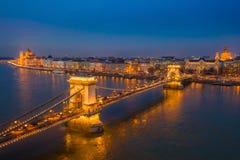 Budapest, Ungarn - Vogelperspektive der ber?hmten belichteten Szechenyi-H?ngebr?cke an der blauen Stunde mit Parlamentsgeb?ude lizenzfreie stockbilder