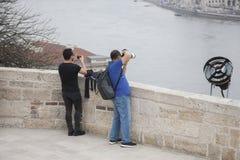 Budapest Ungern - April 10, 2018: Den manliga turisten med en digital kamera står på fyrkanten och tar bilder av sikten royaltyfri bild
