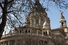 Budapest Ungern - 02/19/2018: Domkyrka för St Stephen ` s med gör bar trädförgrund mot klar blå himmel Religiös arkitektur Royaltyfria Bilder