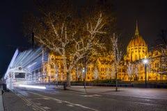 Budapest Ungern - Festively dekorerad ljus spårvagn Fenyvillamos på flyttningen med parlamentet av Ungern på den Kossuth fyrkante arkivbild